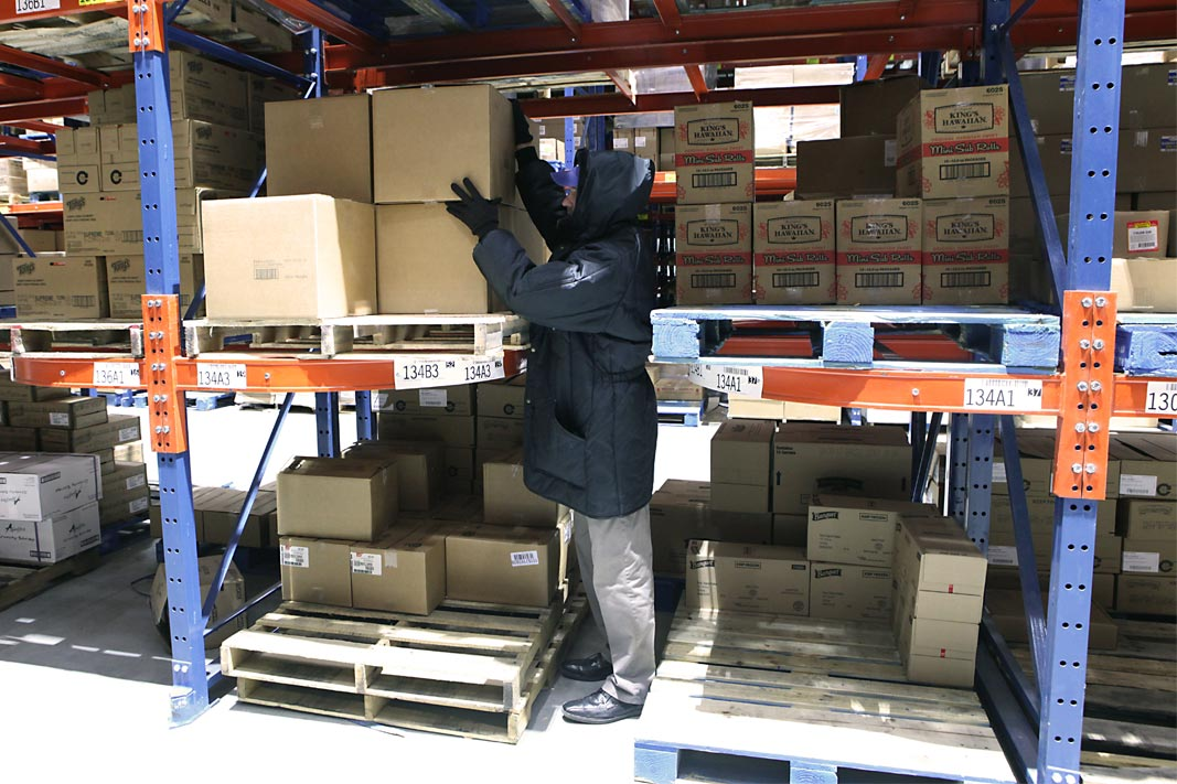 A worker picks a case from Ergo-Label Beam® pallet racking.