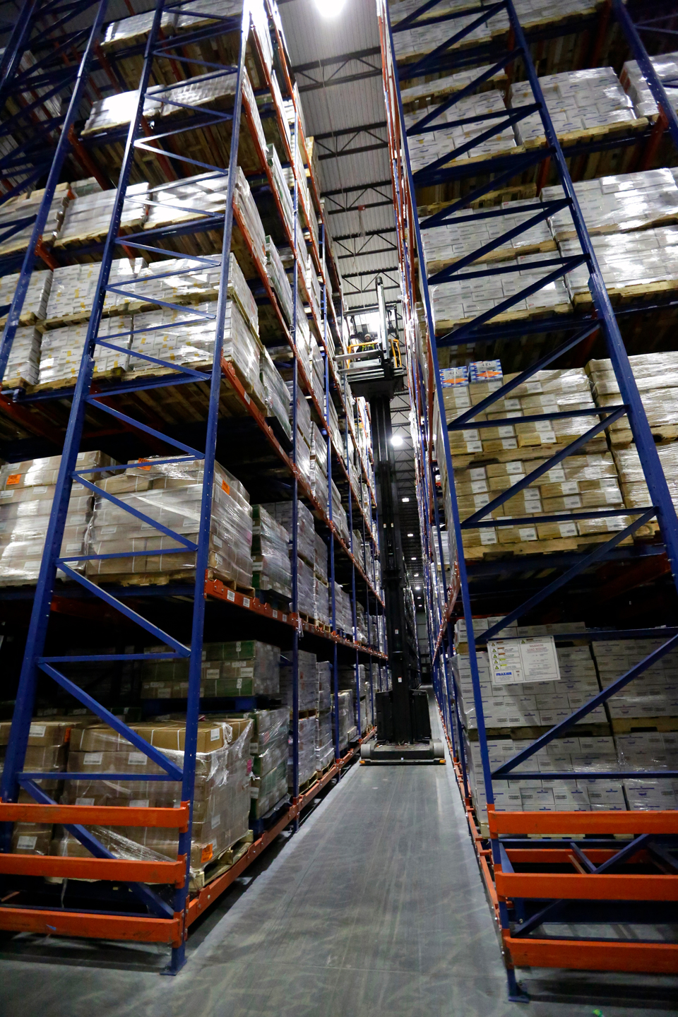 A fork truck travels down aisle in a VNA Push Back Racking System.